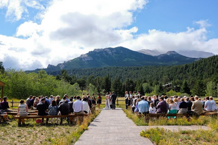 Couple getting married in front of the Rocky Mountains at Wild Basin Lodge in Allenspark, Colorado