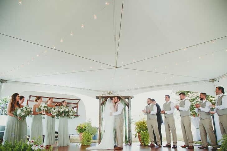 When it rained before the start of the ceremony, Natalie and Michael moved their ceremony inside a large white tent. Their homemade wooden altar was moved from the original spot by a willow tree to inside the tent, beside dramatic planters overflowing with greens.