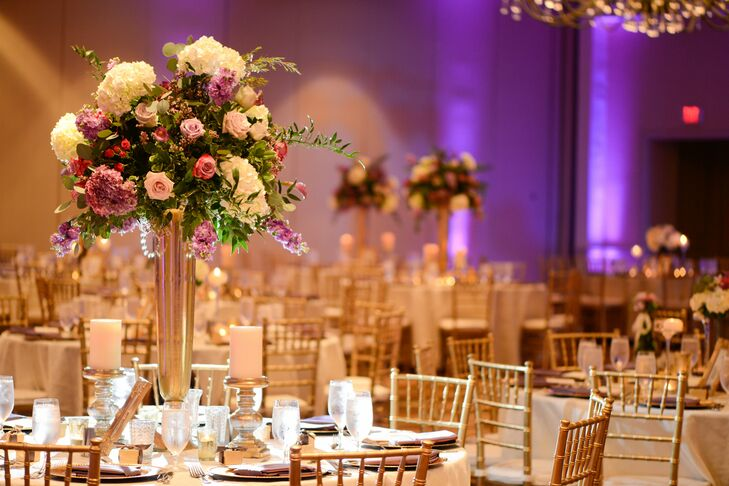 Purple and white hydrangeas, stock and spray roses burst from tall gold vases surrounded by low candelabras.
