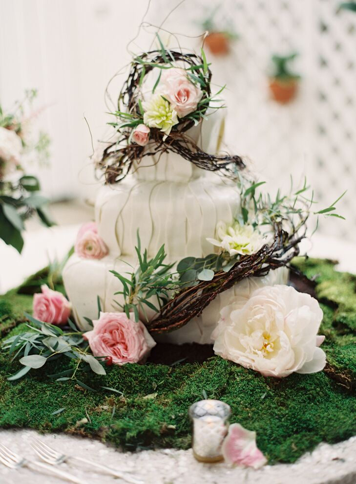"""The couple chose a whimsical garden inspired three-tiered wedding cake baked by Johnson's Custom Cakes & More. It was complemented with cream peonies, pink garden roses and pink ranunculus. """"We wanted the cake to seem as though it were part of the decorated room, and not a foreign piece of focus,"""" says Joyce."""