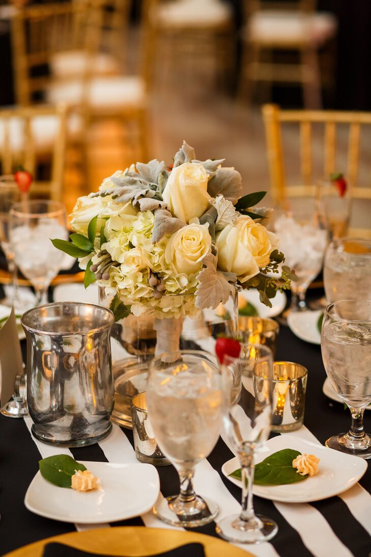 The bridal bouquet served as the centerpiece for the sweetheart table, filled with a variety of ivory roses and hydrangeas.