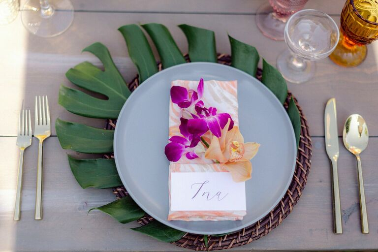 Tropical place setting with monstera leaf charger and orchid accents