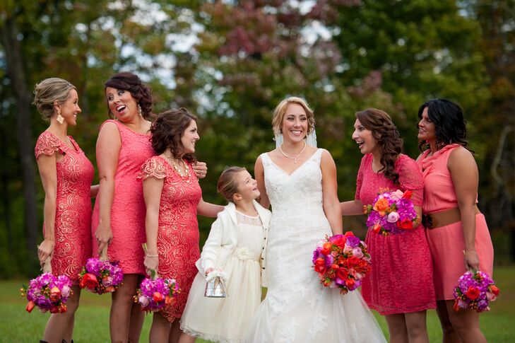 Megan's bridesmaids wore different styles of knee-length dresses in dark coral. They styled their hair down and carried fuchsia and purple bouquets.
