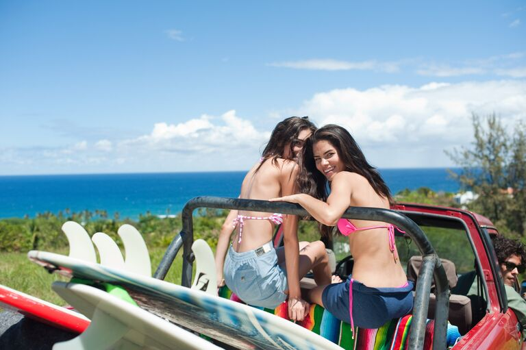 two women sitting in an open-top jeep with surfboards