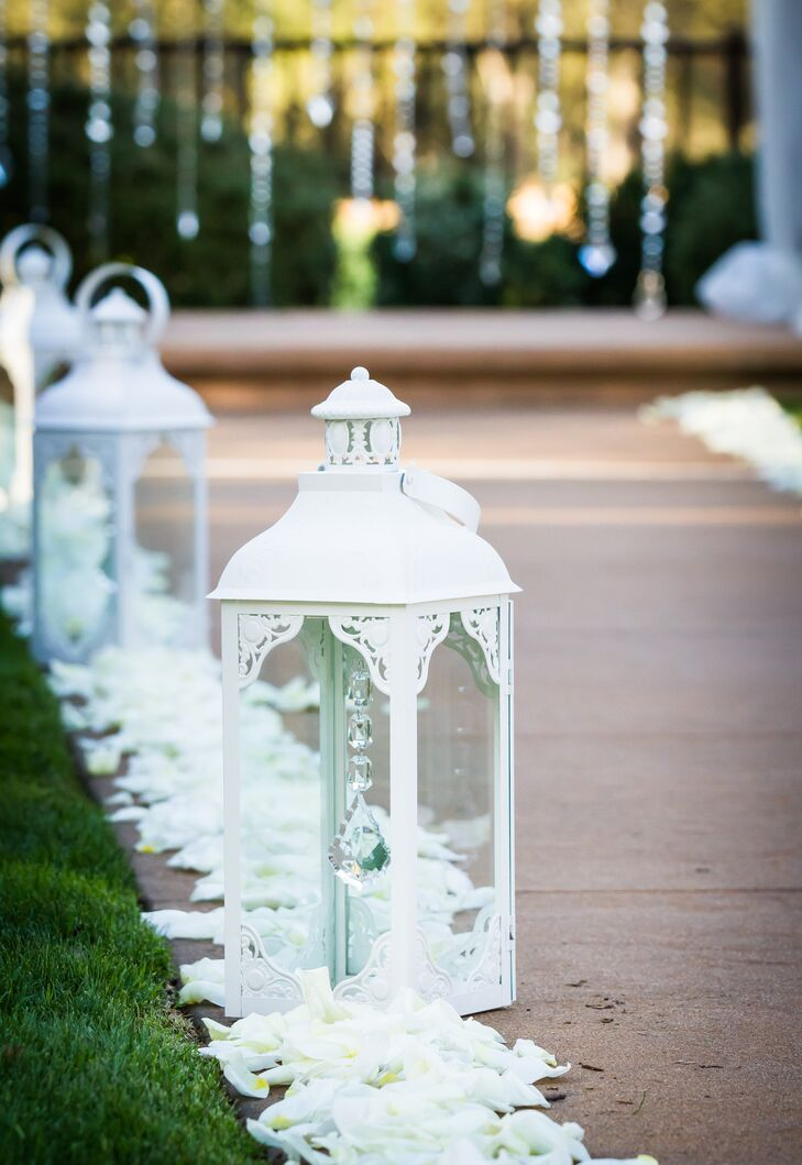 At the outdoor ceremony, the aisle was lined on both sides with white petals and tall elegant lanterns. This led to the wedding arch, which was draped with white linens and dangling crystals hanging down the middle.