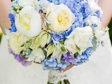 Blue and white wedding bouquet with peonies, roses, irises, tweedia and hydrangeas