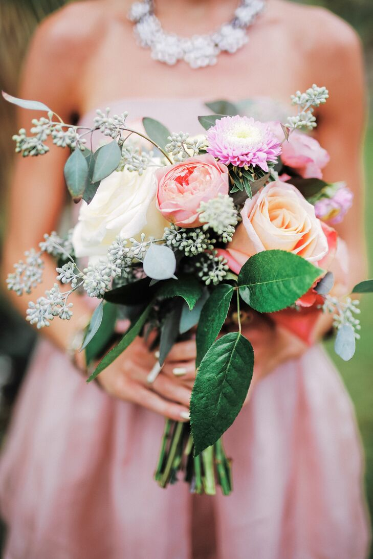 Bridesmaid bouquets were made with pink and yellow garden roses, peonies and leafy greenery.