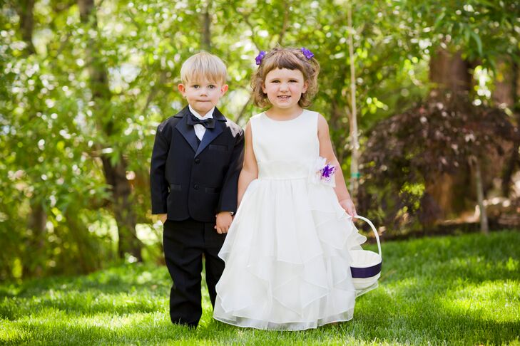 The flower girl and ring bearer dressed formally for the outdoor wedding. The ring bearer wore a classic black tuxedo, and the the flower girl donned a white dress with a ruffled organza skirt and purple floral accents.