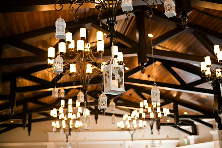 KIS Events, the couple's wedding planner, added a vintage and welcome touch to the venue's wooden ceiling. Black chandeliers were complemented with hanging neutral lanterns. Each accent had a subtle floral design that paired nicely with the couple's rose, stargazer lily and greenery-accented centerpieces.