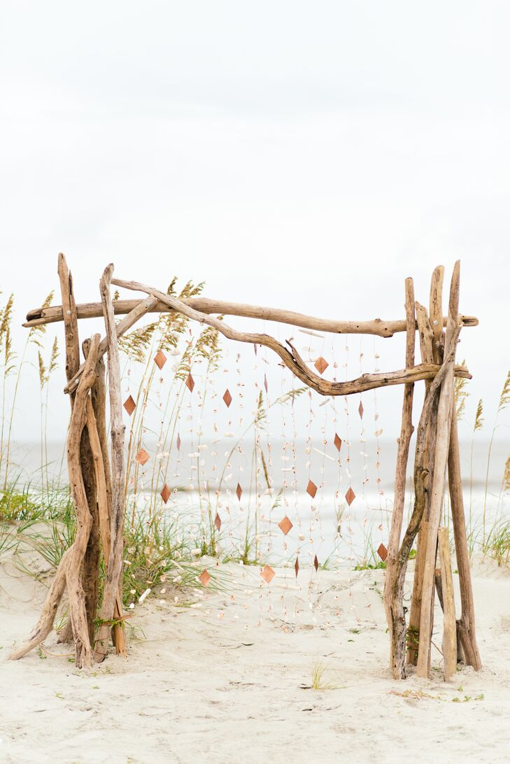 Noelle put her artistic creativity to work, handcrafting many of the wedding's decorative details herself. While the couple decided to keep things simple for the ceremony, allowing guests to full appreciate the beauty of the waterfront locale, Noelle created a stunning driftwood wedding arch draped in garlands of tiny white sea shells in front of which the couple exchanged vows.