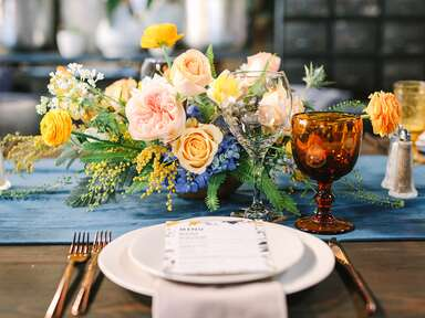 rustic wedding tablescape with gold plates and blue flowers