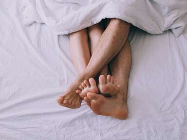 woman and man's legs and feet tangled up in bed