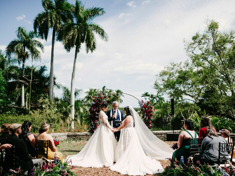 Brides saying vows during outdoor tropical wedding ceremony