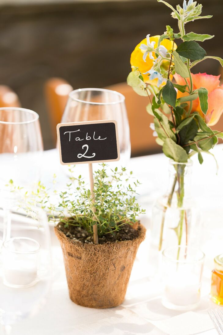 The chalkboard table numbers were stuck in small, potted rosemary plants.