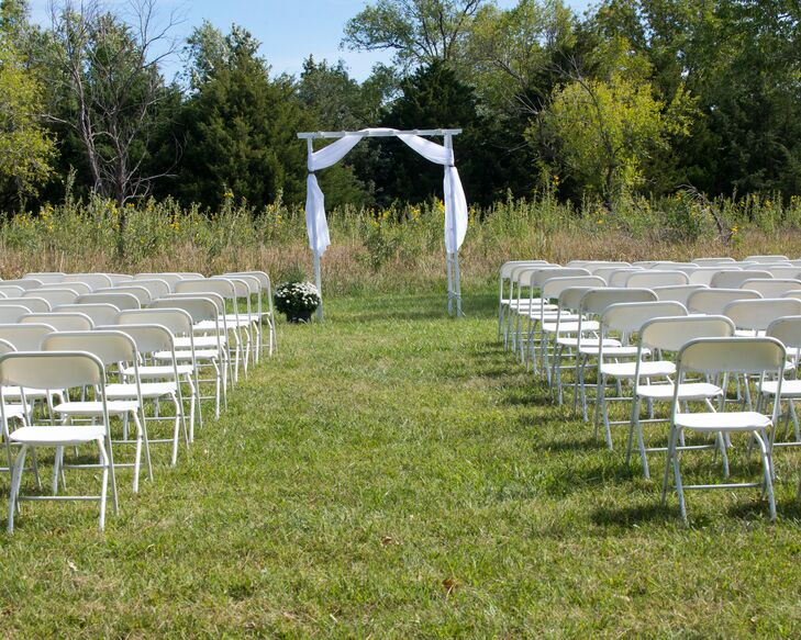 The couple exchanged vows in an open space in the park with wildflowers growing in the background. The wedding arbor was simple and white and decorated with white drapery for a more romantic feel.