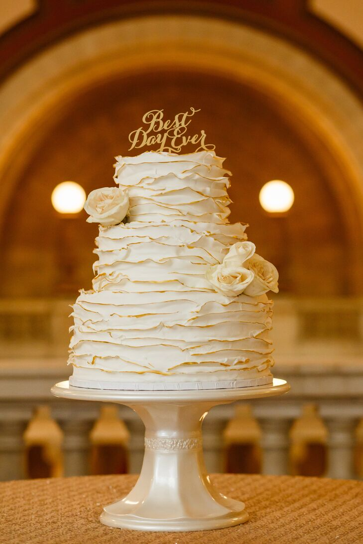 """The three-tiered main wedding cake was pumpkin spice with cream cheese frosting. The cake was accented with ivory roses and had a cake topper that read """"Best Day Ever."""""""