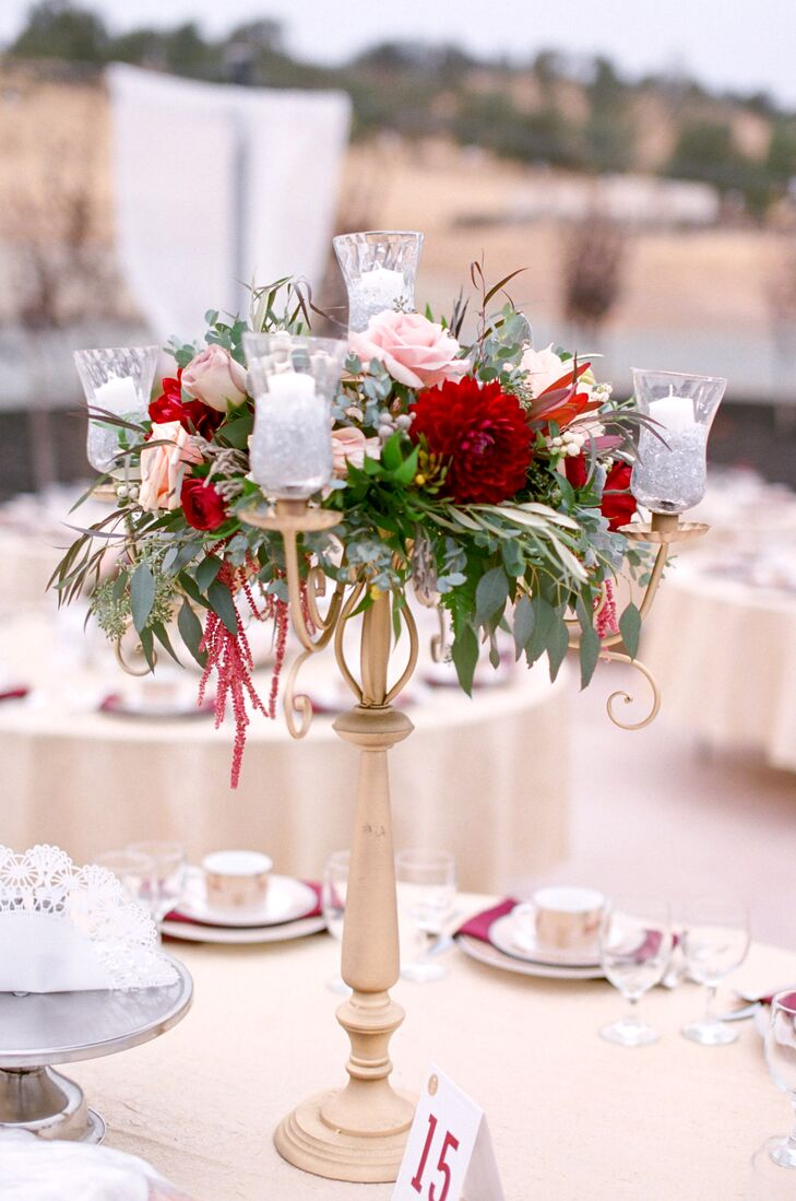 At the reception, each table was set with a golden, midheight candelabra from which greenery and garden roses overflowed.