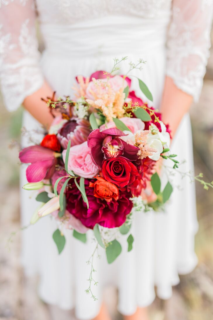 """The florals were the crowning jewel of the day, infusing life and energy into the decor. Lindsay, a florist, took all the wedding's flowers into her own hands and, with the help of her assistants, created standout arrangement after standout arrangement. """"My favorite thing about a bouquet is texture—lots and lots of texture,"""" Lindsay says. """"So I chose classic bridal blooms like peonies, astilbes and garden roses, and threw in unexpected items like proteas and kangaroo paws to add a little spice."""""""