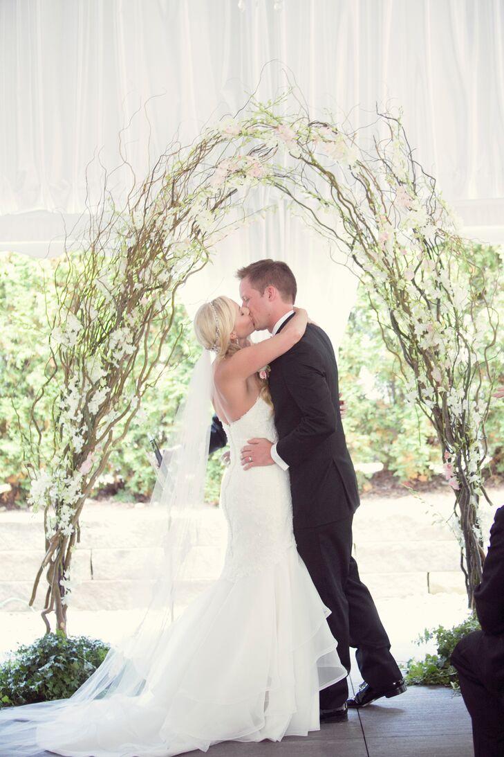 First Kiss Under White Branch Wedding Arch