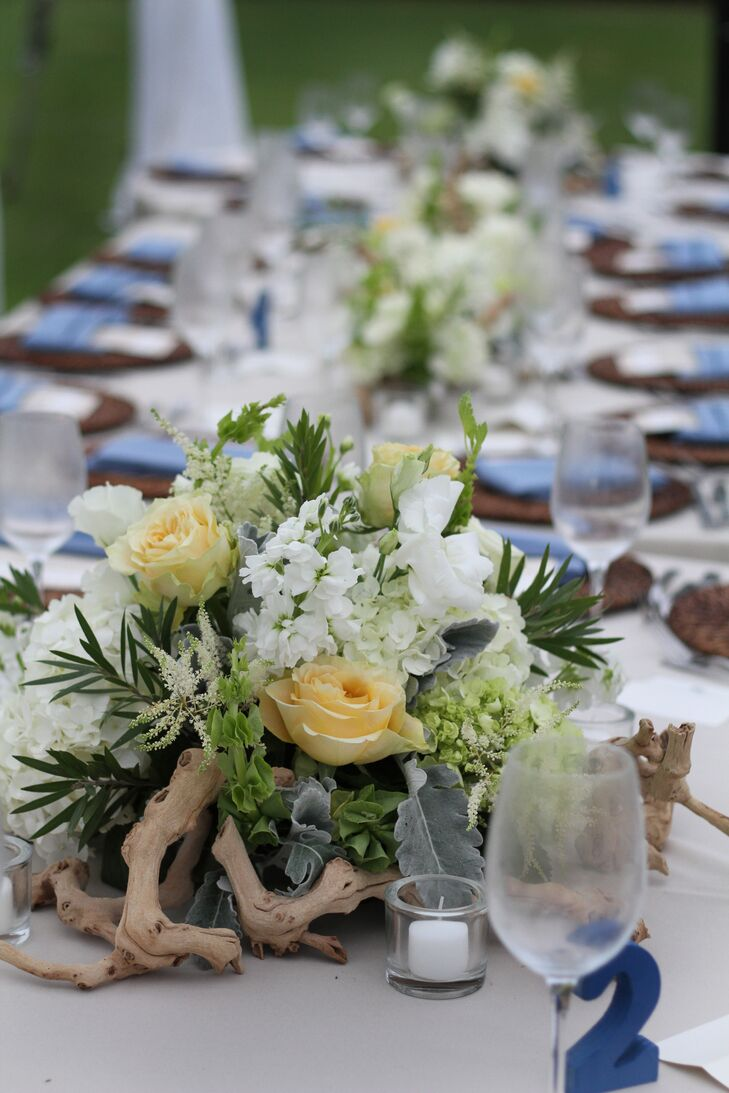 The couple decorated each table with unique centerpieces of curly willow branches, white bottlebrush, grapevine wood, yellow roses, dusty miller and white lisianthus.