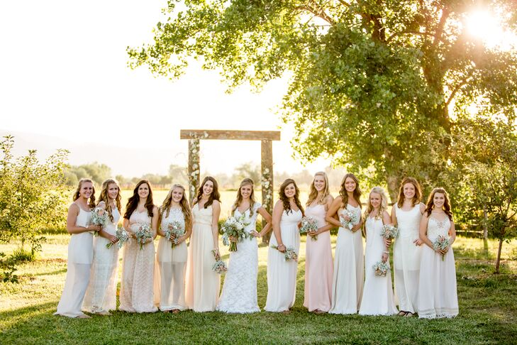 """Leslie let her 11 bridesmaids wear whatever made them comfortable for the rustic farm wedding. She asked them to find a casual maxi dress in a light neutral color. """"They all did an amazing job finding the perfect dresses,"""" Leslie says. """"I'm so happy with the way they looked together."""" Each of the ladies completed their look with simple jewelry, soft curls and sandals."""