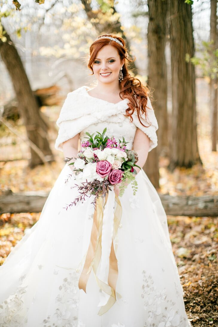 Amanda wore a stunning Justin Alexander ball gown with beading and embellishments in the skirt. She carried a bouquet with white and jewel-toned flowers that was tied with gold ribbon, and she wore a white stole to keep her warm in the fall weather.