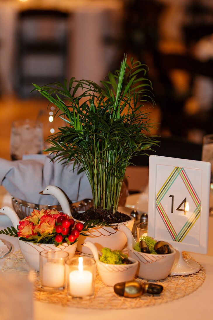 Neanthe bella palm plants, mambo spray roses and red hypericum berries with leather leaf fern and groupings of reindeer moss with gold painted rocks were each nestled in a ceramic measuring cup. White table numbers had the evening's menu printed on the other side.