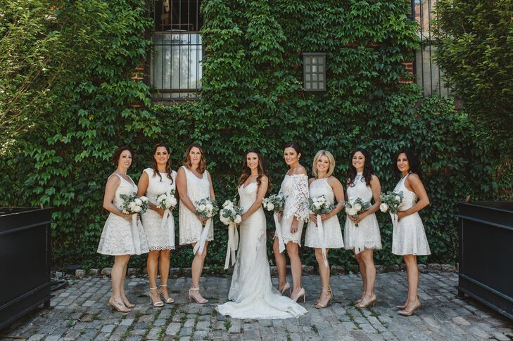 "Keeping with the day's crisp white palette, each of Nancy's bridesmaids wore a different lacy white knee-length dress. ""I wanted them to like their dress and feel comfortable,"" Nancy  says. Bouquets were made with white peonies and roses and eucalyptus and lemon leaves."
