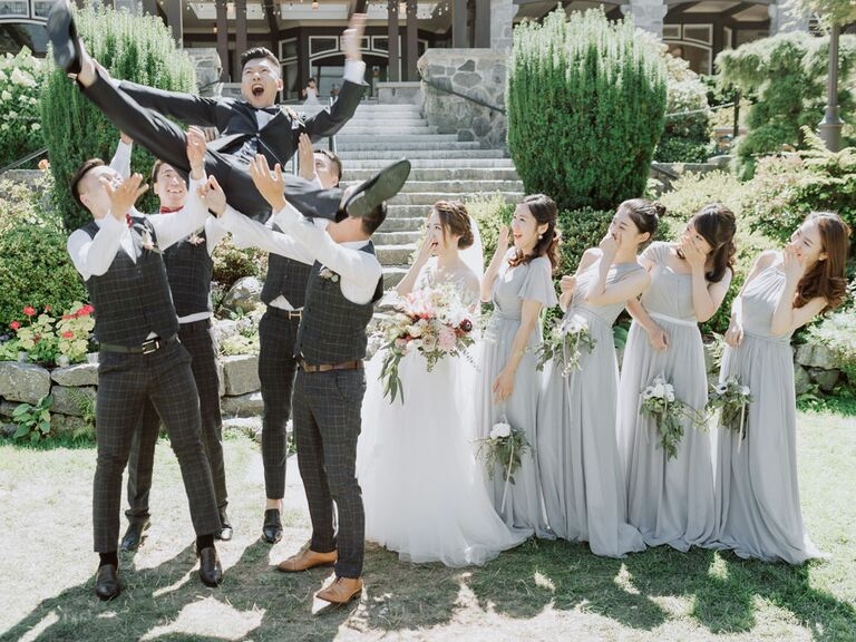 Funny groom and groomsmen photo with groomsmen throwing groom in the air