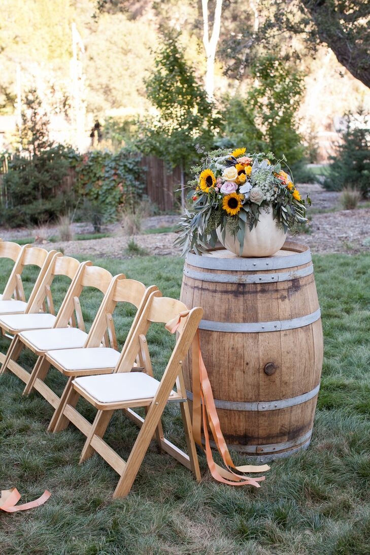 Light wooden folding chairs faced the front of the ceremony space where the couple were married. The chairs on the end that lined the aisle were tied with orange pieces of ribbon. Lush sunflower and rose arrangements were placed inside white pumpkins to go along with the fall theme and season, which were propped up on a wooden barrel.