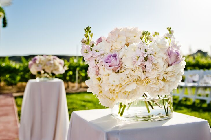 The aisle was lined with white hydrangeas, purple roses and stock arranged in glass vases, positioned on top of tall tables covered in white linens.