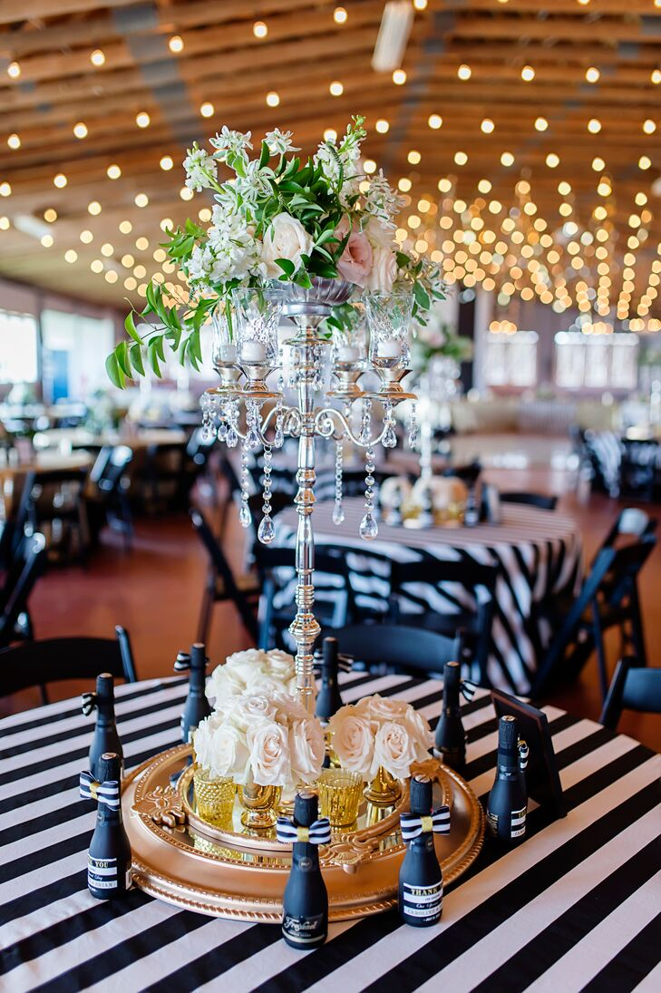 To create glitzy reception centerpieces, tall candelabras were covered in crystals and draping greenery. Blush and ivory roses were added throughout the venue to contrast with all the black and white decor and give the celebration an elegant Kate Spade feel.