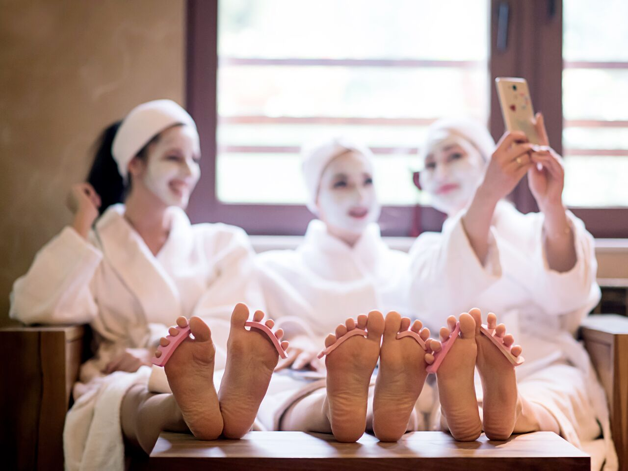 Three ladies getting facials and pedicures while taking a selfie