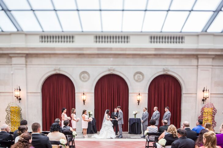 "Elon and Justin stood at the altar surrounded by their wedding party during their ceremony, which took place at the Columbus Museum of Art in Columbus, Ohio. ""The glass ceiling of the museum provided us with a feel of being outdoors without having to worry about rain,"" the couple says. ""It turned out to be a great decision as it rained up until our ceremony that day."""