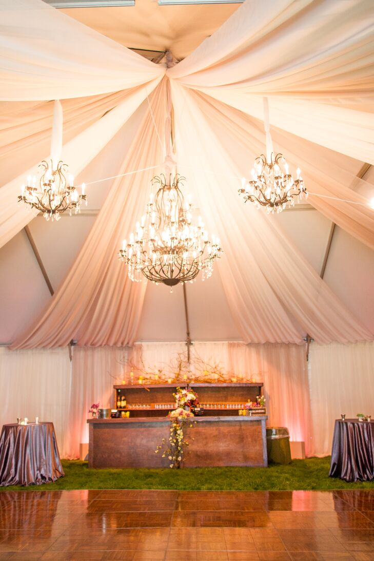 The reception tent was decorated with white and plush pink drapery, and lit by gold chandeliers.