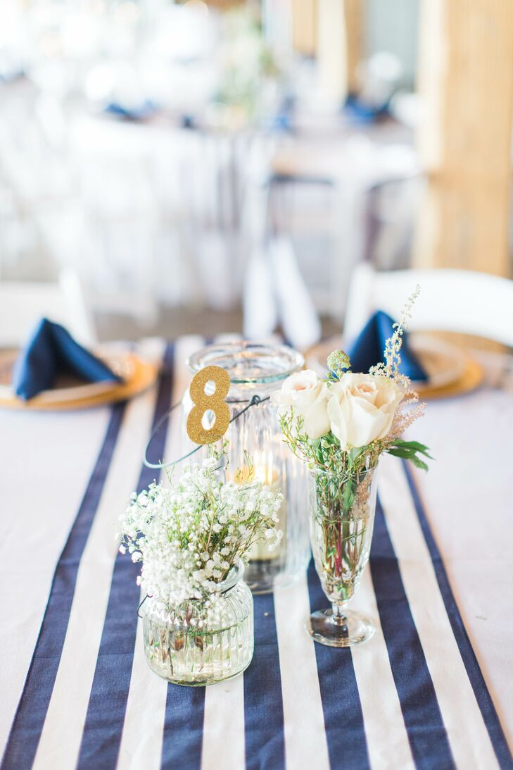 Each table had gold chargers, navy napkins, and a navy striped runner with assorted glass pitchers, vases and lanterns in the center.  Each vase or pitcher held an assortment of blush colored blooms around a small gold table number.