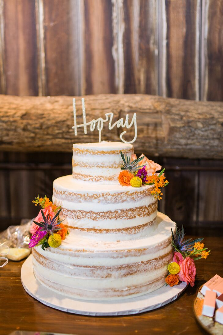 "Dreamscape Desserts whipped up this vanilla naked cake with a raspberry filling for Molly and Visar's reception. Bright flowers and a cheeky cake topper made this treat even sweeter. ""It was exactly what we wanted,"" Molly says of the three-tier confection."