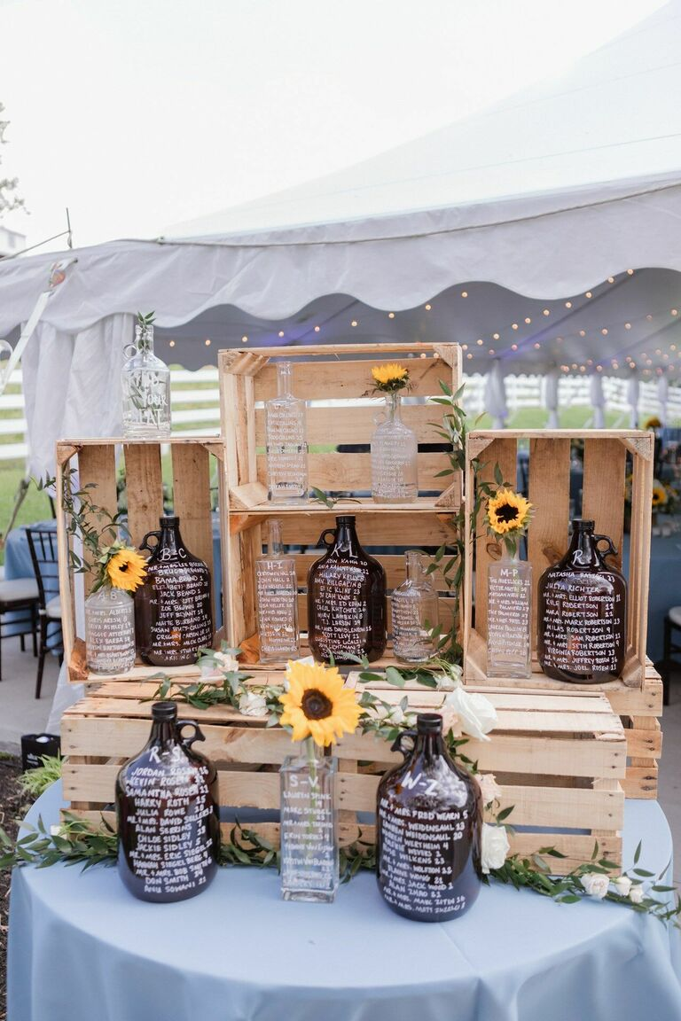Seating chart display with crate and bottles accented by sunflowers