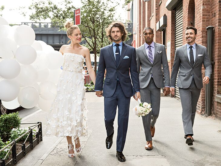 bride with balloons, groom in blue suit and groomsmen in gray suits