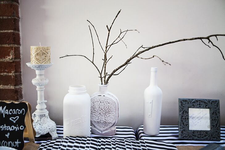 A glass vase was filled with branches on a striped table, surrounded by other vases painted white and a candle.