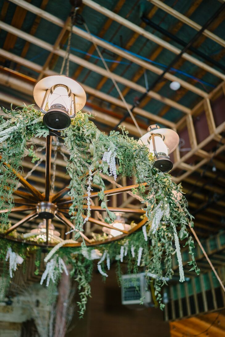 Adding to the day's Polynesian flair, tropical green garlands were hung from the chandeliers in the barn of the indoor-outdoor reception at Quiet Meadow Farm in Mapleton, Utah.