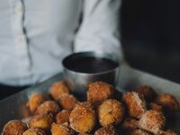 Cinnamon doughnut holes with a sugary dipping sauce