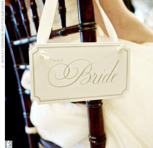 Hanging bride and groom signs were playful additions to Dixie and George's reception chairs—and let guests know where the couple would be sitting.