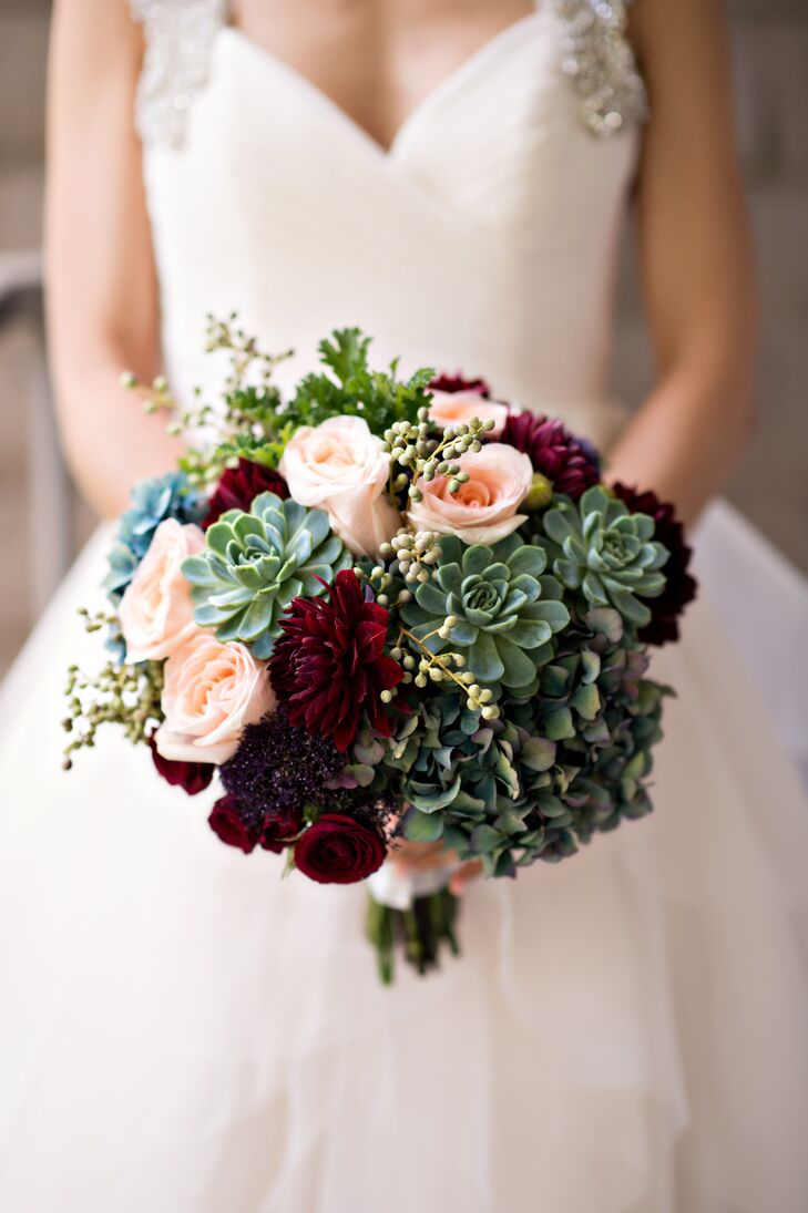 """I just wanted our wedding to be simple and romantic, so we went with a lot of candles to add some sparkle and white flowers with a touch of burgundy for the floral arrangements,"" Lauren says. For the bridal bouquet, Blossom Floral created a bountiful bundle of succulents, hydrangeas, scabiosas, dahlias and roses in dramatic shades of burgundy, blush, purple and green that popped against the pale blush organza of Lauren's Hayley Paige dress."