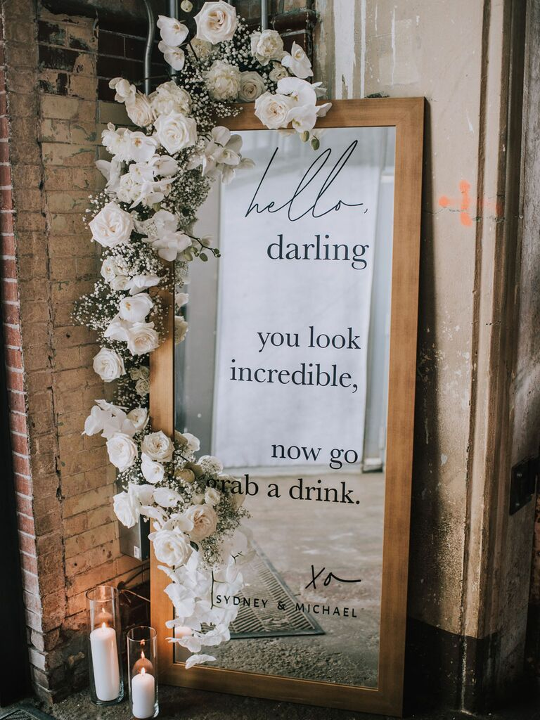 Mirrored wedding signage with white floral garland decoration