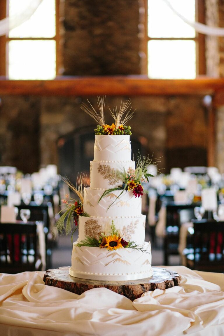 Five-tier wedding cake with mountain and sunflower accents