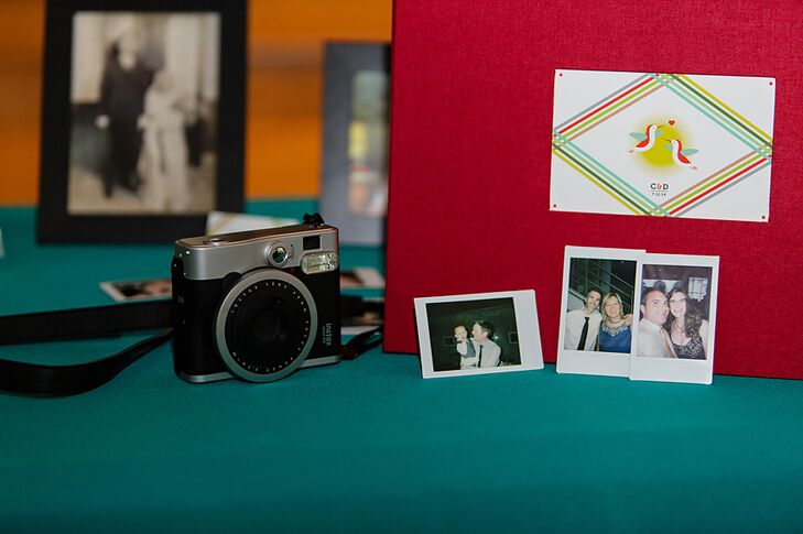 A red guest book was placed on a table decorated with family photos and an instant camera.