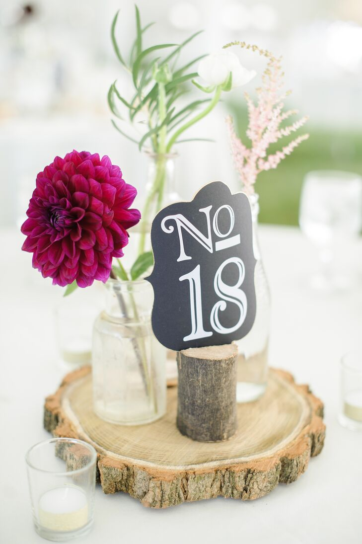 Playing up the vintage-rustic theme, reception centerpieces featured three vintage glass bottles filled with simple stemmed florals placed on a decorative slice of tree trunk.