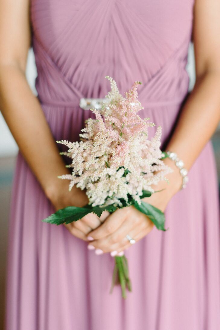 The bridesmaids bouquets captured their romantic looks with a simple arrangement. Anna Rose Floral and Event Design filled each arrangement with blush and pink astilbes and greenery for texture. The lighter-hue flowers went nicely with their dresses.