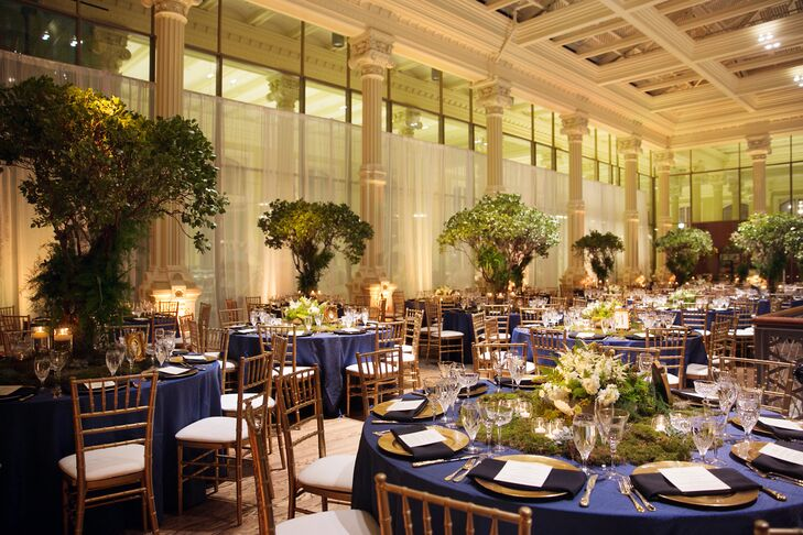 """Drawing on the venue for inspiration, as well as what Linsey refers to as """"the eerie feel"""" of the season, the couple dreamed up an enchanted woodland theme for the evening, complete with a rich color palette of moody black and blue hues, statement-making moss, succulent and floral centerpieces made by Poppies Design Studio and plenty of gilded details and warm candlelight. """"Visually, I wanted people to feel like they were in the woods and stumbled upon some dream-like dinner party,"""" says Linsey"""